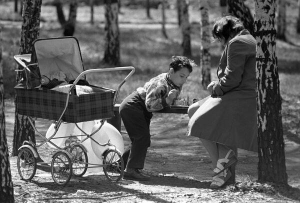 Городской парк Сокольники. Мама с сыном играет в шахматы
