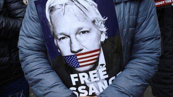 Плакат в руках активиста во время акции в поддержку Джулиана Ассанжа