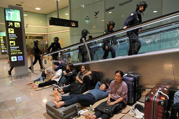 Испанские полицейские проходят мимо пассажиров, ожидающих в аэропорту Эль-Прат в Барселоне
