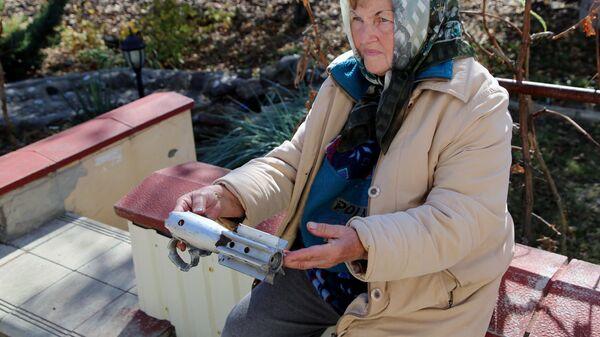 Жительница поселка Ясное демонстрирует осколки снаряда, найденные на месте обстрела, в поселке Ясное Донецкой области