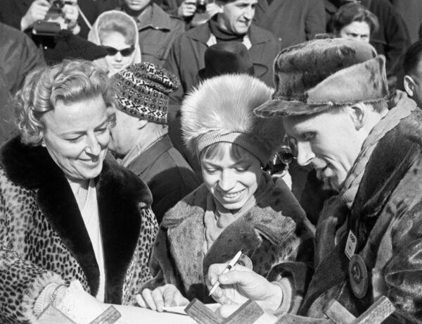 Чемпионы Олимпийских игр по фигурному катанию Людмила Белоусова (в центре) и Олег Протопопов дают автографы