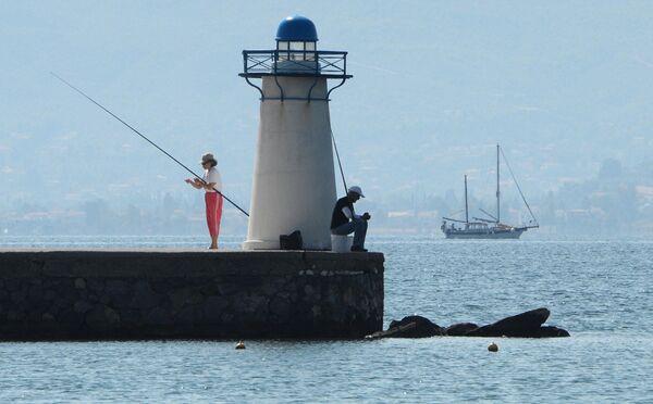 Отдыхающие ловят рыбу возле маяка в заливе Нотиос-Эввоикос Эгейского моря