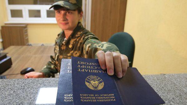 Пограничник проверяет паспорта на пограничном переходе между Белоруссией и Польшей Переров