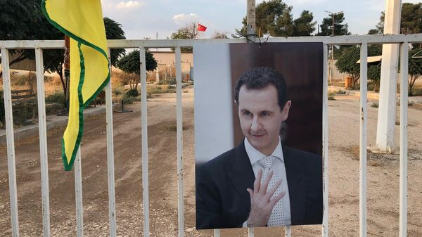 Портрет президента Сирии Башара Асада на фоне флага Турции и курдских сил самообороны (YPG) на КПП на сирийско-турецкой границе в городе Кобани