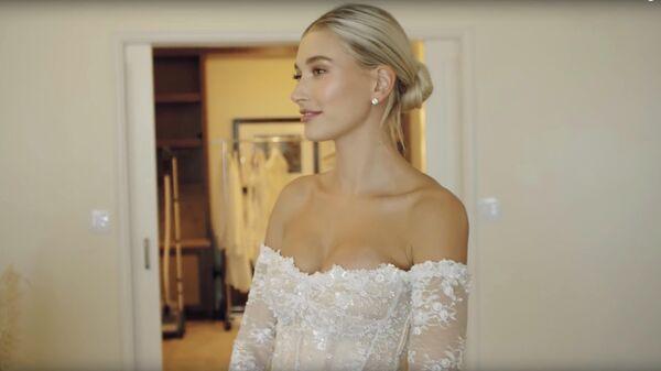 Стоп-кадр видео примерки свадебного платья американской моделью Хейли Род Бибер