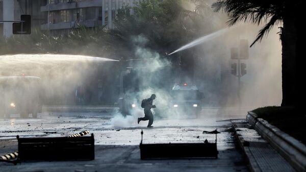 Протестующий во время акции протеста в Сантьяго
