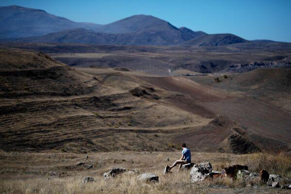 Турист на территории мегалитического комплекса Караундж, находящегося на юге Армении, вблизи города Сисиан