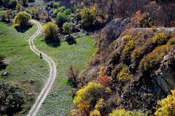 Человек прогуливается по дороге близ озера Севан в Армении