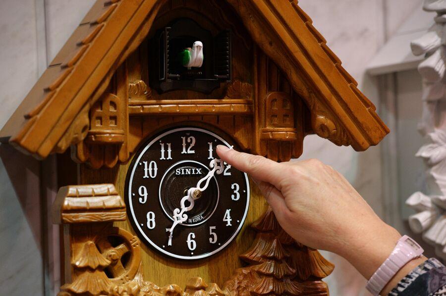 Продавщица демонстрирует настенные часы в магазине Время в Новосибирске