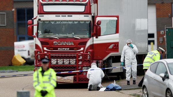 Полицейские у грузовика, в котором были обнаружены телами, в британском городе Грейс