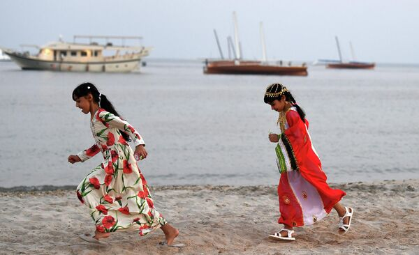 Девочки бегают по берегу острова Далма, ОАЭ