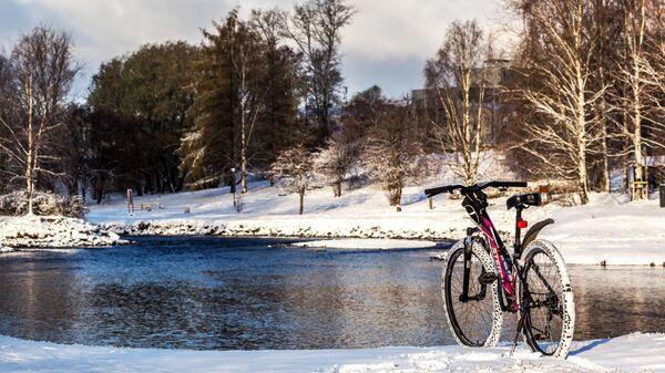 Велосипед на заснеженной велодорожке на берегу реки Лососинки в центре Петрозаводска
