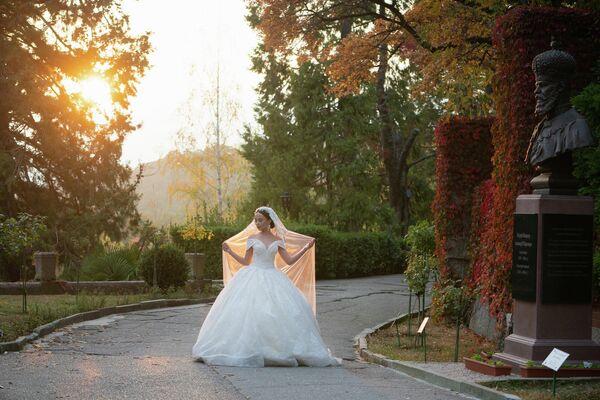 Крым. Территория Массандровского дворца. Невеста фотографируется у бронзового бюста императору Александру III