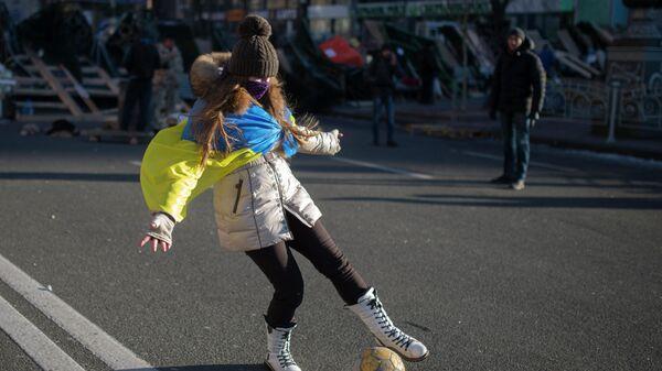 Девушка играет с мячом на улице Крещатик в Киеве