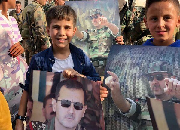 Дети с плакатами с портретом президента Сирии Башара Асада в освобожденном сирийской правительственной армией городе Манбидж в Сирии