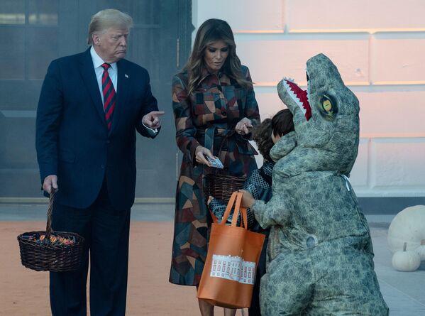 Президент США Дональд Трамп и первая леди Мелания раздают детям конфеты на праздновании Хэллоуина в Белом доме