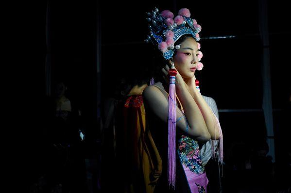 Модель перед показом коллекции модной марки David Sylvia, созданной дизайнером Hao Weimin на Неделе моды в Китае
