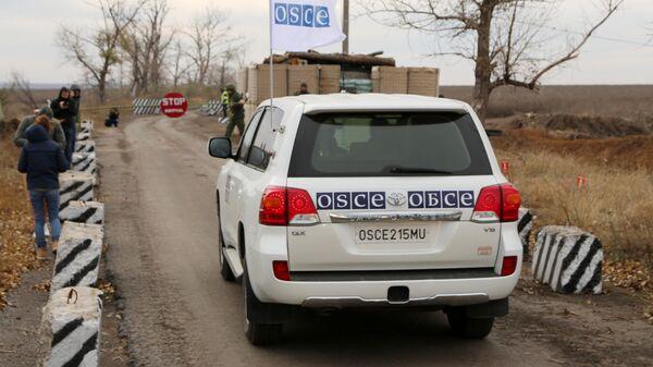 Автомобили специальной мониторинговой миссии ОБСЕ в селе Петровское в Донецкой области, где должен состояться отвод сил бойцов подразделений  ДНР