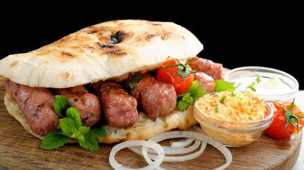 Чевапчичи на гриле с маринованным красным перцем и творожным сыром каймак, подается с лепешкой лепинья