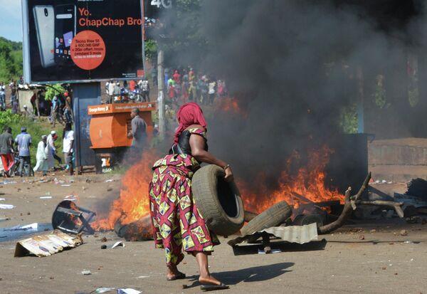 Женщина жжет шины во время похорон после уличных протестов в Конакри, Гвинея