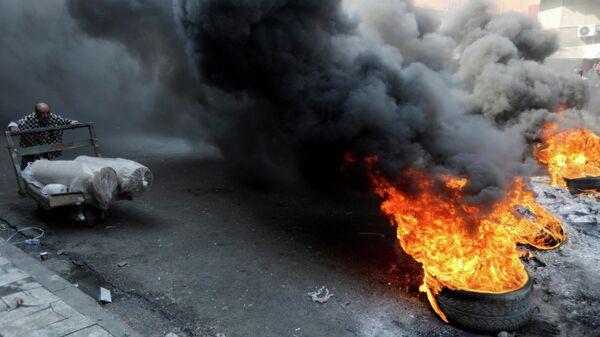 Демонстранты жгут покрышки во время акция протеста в Багдаде, Ирак