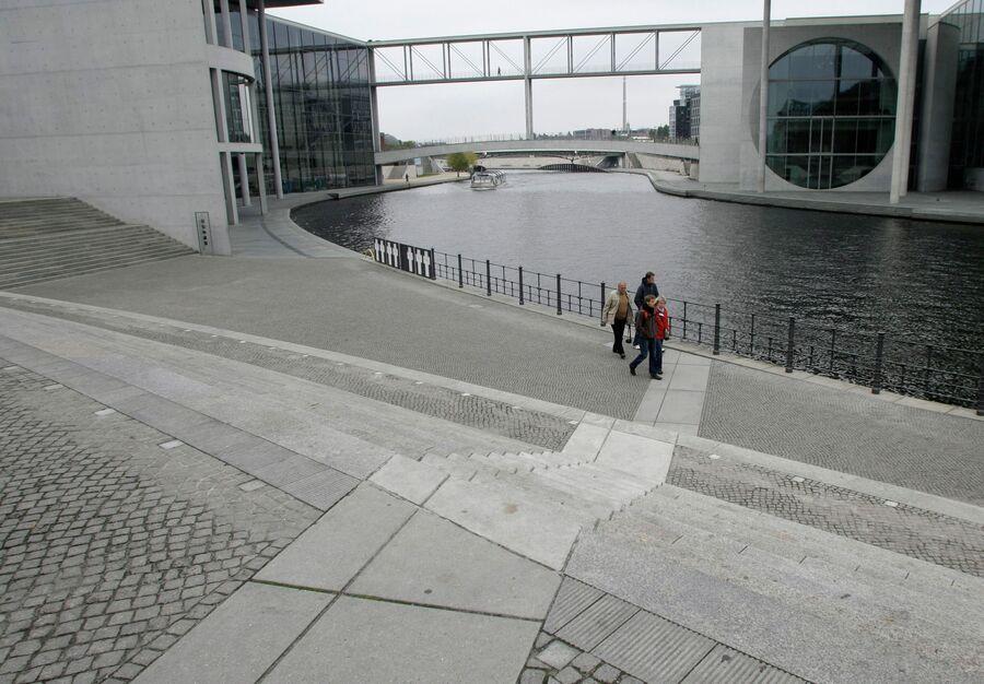 Туристы идут по историческому маршруту Berliner Mauerweg, проходящему на месте расположения Берлинской стены