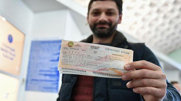 Мужчина демонстрирует купленный билет на железнодорожном вокзале в Симферополе