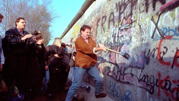 Житель Западного Берлина разрушает стену. 1989 год