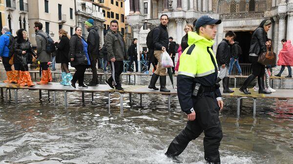 Туристы на площади Сан-Марко в Венеции во время наводнения