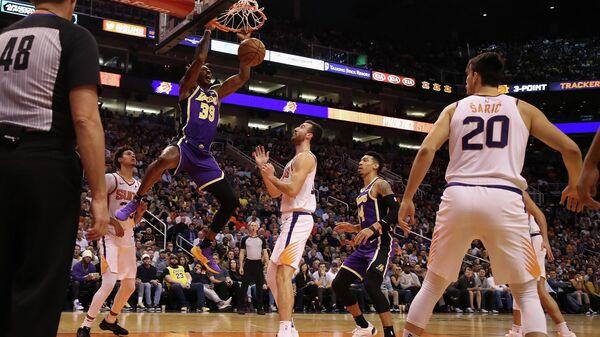Игрок ХК Лос-Анджелес Лейкерс Дуайт Ховард забрасывает мяч в корзину в матче против ХК Финикс Санз