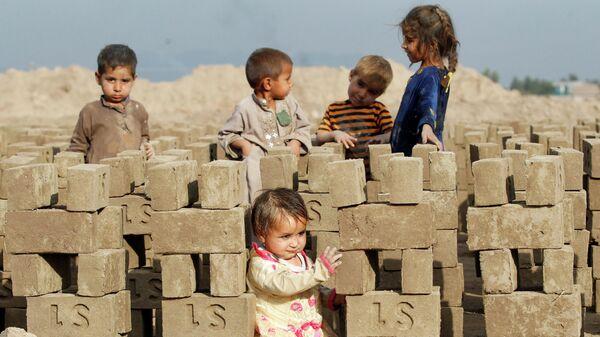 Афганские дети играют на кирпичном заводе на окраине Джелалабада