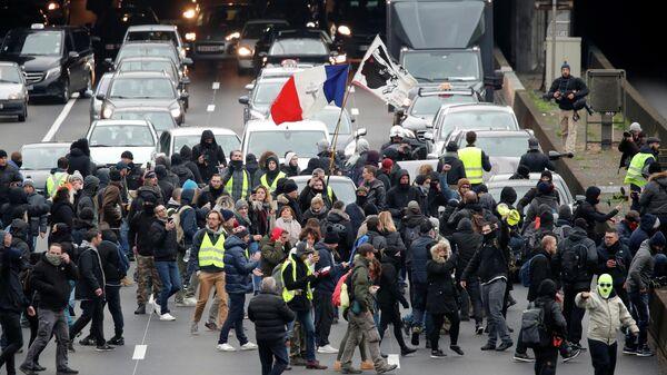 Протестующие во время демонстрации движения желтых жилетов в Париже