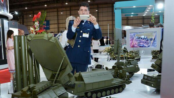 Посетитель выставки осматривает макеты военной техники, представленные на стенде АО Рособоронэкспорт на международном авиасалоне Dubai Airshow 2019 в Дубае