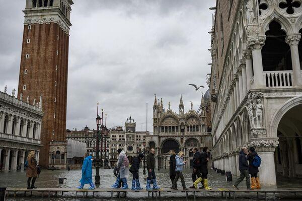 Прохожие в окрестностях площади Сан-Марко в Венеции во время наводнения