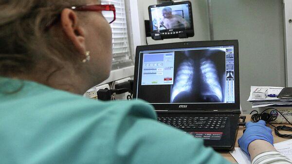 Врач рассматривает снимок грудной клетки пациента