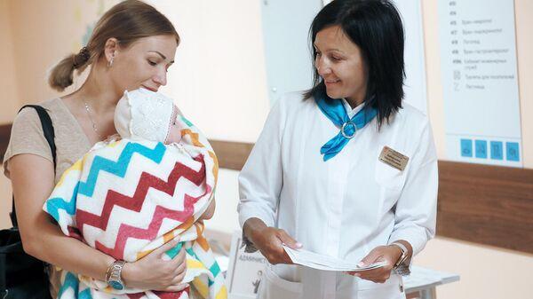 Мама с ребенком общается с сотрудником поликлиники