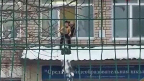Стоп-кадр видео чистки снега с козырька школы в Приморье ребенком