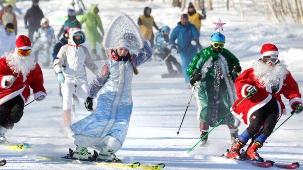 Участники массового спуска в карнавальных костюмах с горы Морозной в Камчатском крае
