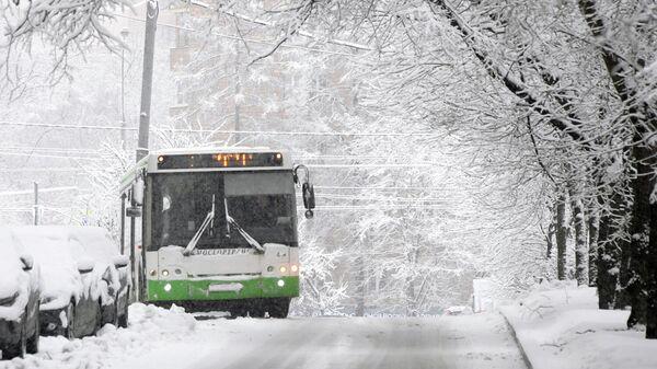 Автобус движется по заснеженной улице