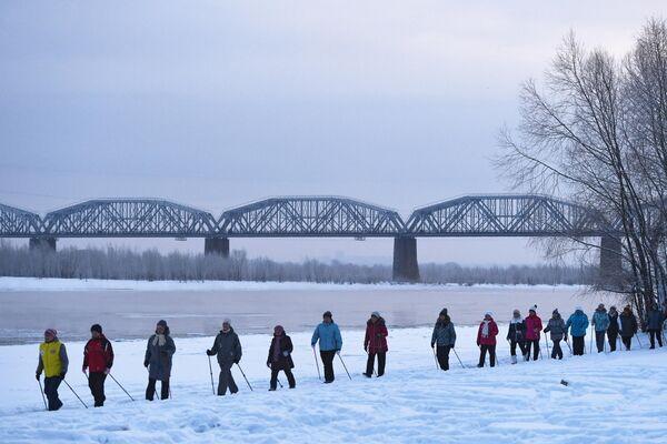 Женщины во время проведения бесплатных занятий по скандинавской ходьбе на берегу реки Обь в Новосибирске