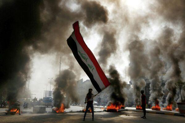Протестующий размахивает флагом Ирака во время антиправительственной акции в Ан-Наджафе