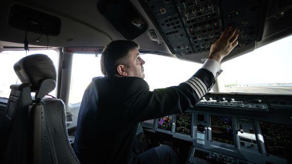 Пилот в кабине самолета Сухой Суперджет 100 (SSJ-100) в аэропорту Домодедово
