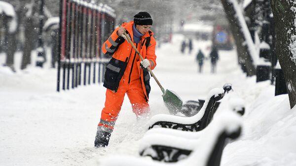 Сотрудница коммунальных служб убирает снег