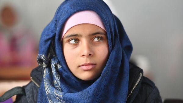Девочка на уроке в школе в лагере беженцев Хирджилла вблизи Дамаска