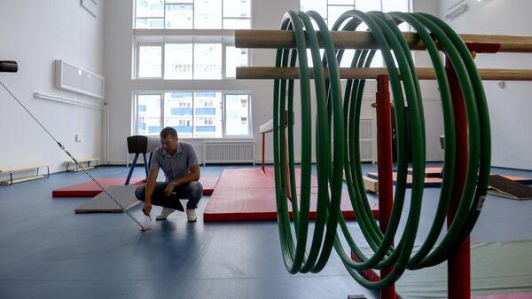 Учитель физкультуры осматривает новый спортзал
