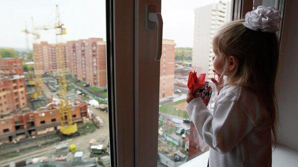 Девочка смотрит из окна новостройки