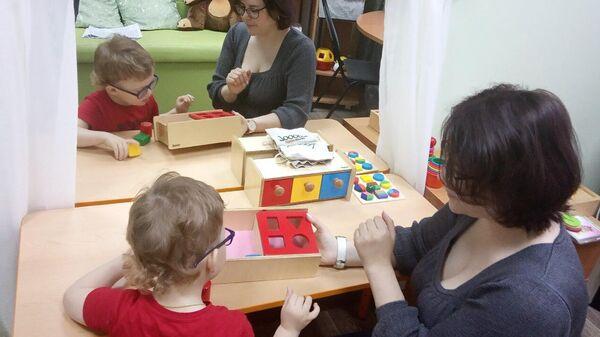 Преподаватель занимается с ребенком в реабилитационном центре