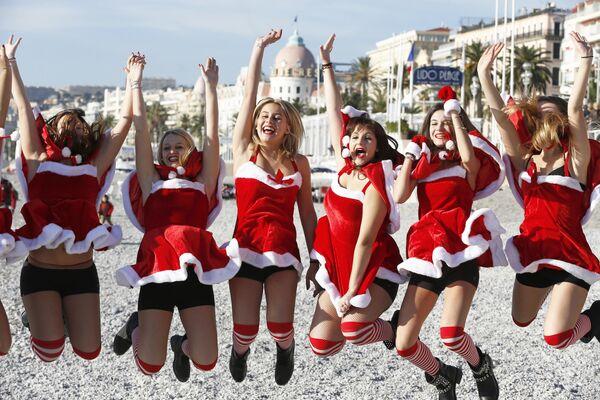 Девушки в костюмах Санта-Клауса на пляже в центре Ниццы