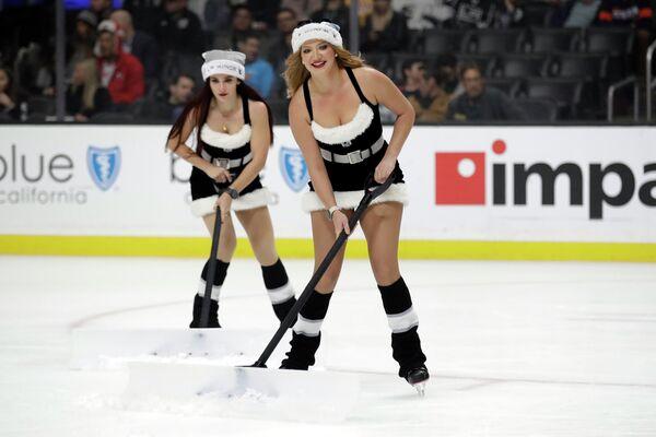 Девушки в костюмах Санта-Клауса на льду во время матча НХЛ в Лос-Анджелесе