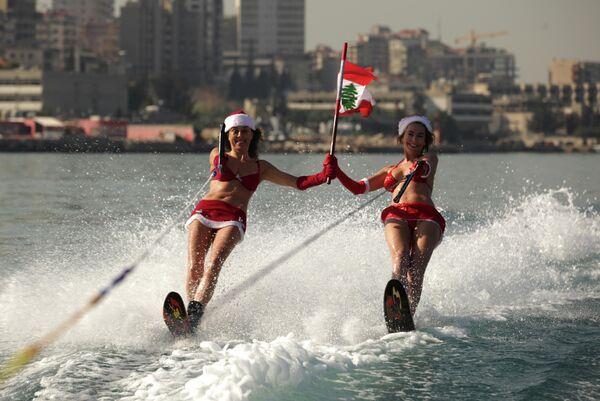 Девушки в костюмах Санта-Клауса катаются на водных лыжах в бухте Джунии под Бейрутом